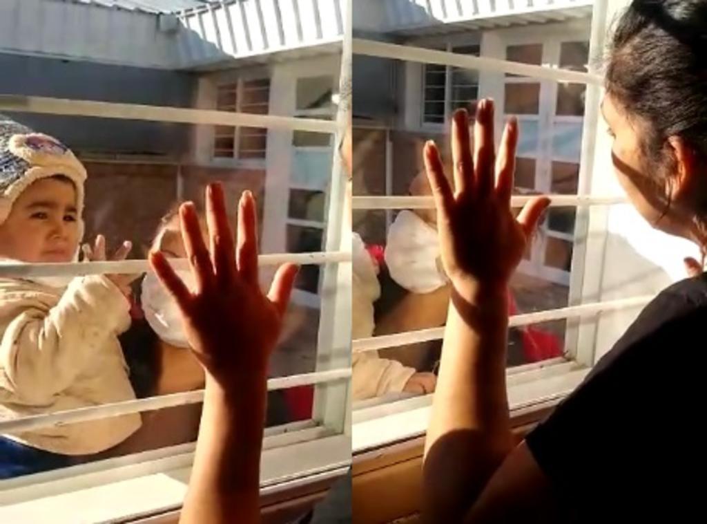 Madre e hijo se reencuentran a través de una ventana por la pandemia