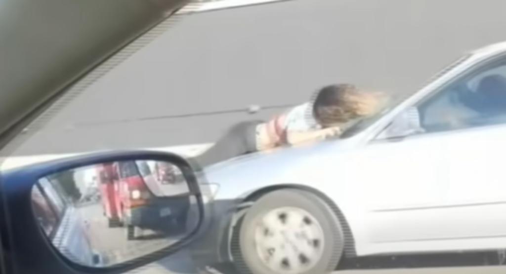 Mujer cuelga desde el cofre de un auto para evitar que se roben a un perro