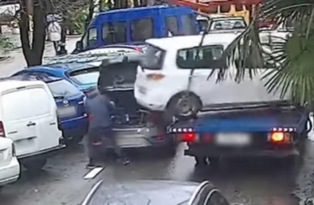 Hombre por poco es embestido por auto que por poco cae de una grúa
